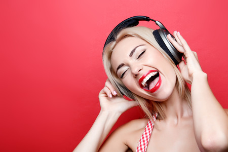 laugher: Favorite song. Smiling young blond-haired girl sloping her head and listening to music while standing on isolated red background