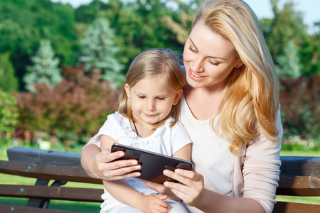 mother on bench: Using technologies. Young pretty mother and her daughter sitting on bench and using tablet.