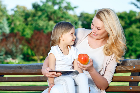 mother on bench: Learning with technologies. Pretty blond-haired mother sitting  on bench with her daughter holding tablet and apple