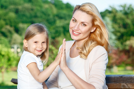mother on bench: Soft touch. Pretty young mother and her little cute daughter sitting on bench and touching hands of each other. Stock Photo