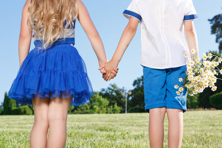 First love. Nice little boy keeping the bunch of flowers  and holding the hands with girl. Stock Photo