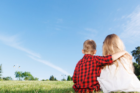 upbeat: Reveling in each other. Little upbeat boy holding his hand on the shoulder of girl while sitting backward with her on grass.