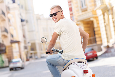 i am here: Here I am. Back view of young handsome blond-haired man wearing sunglasses sitting on scooter Stock Photo