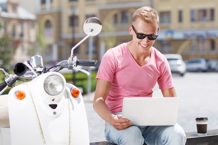 youthful: Communicating with people. Youthful attractive blond-haired man sitting on bench near his scooter and using laptop.