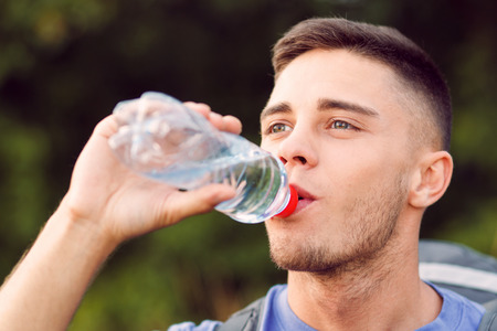 standing water: Close up photo of a young handsome tourist wearing blue t-short and backpack standing, drinking water from the bottle Stock Photo