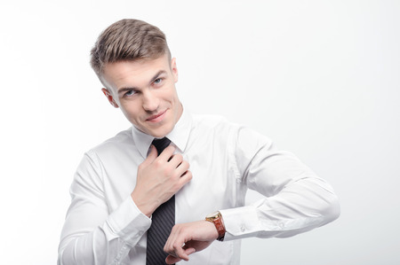 sensational: Getting ready. Young attractive businessman standing on white isolated background fixing his tie and checking time.