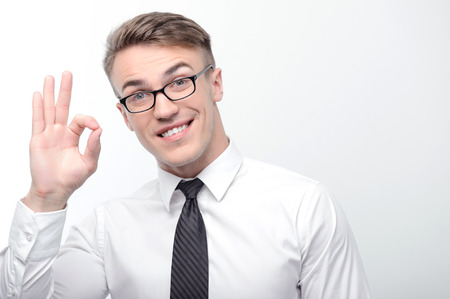 youthful: It is ok. Portrait of youthful attractive happy businessman standing on white isolated background and pointing with his fingers ok.