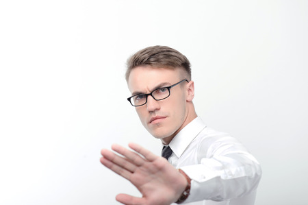 youthful: Stop it. Portrait of youthful attractive serious businessman standing on white isolated background and pointing with his hand.