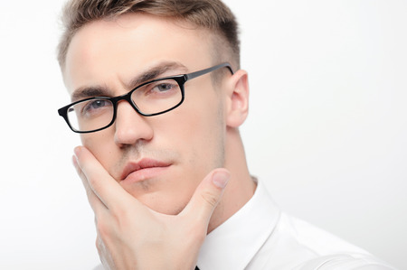 youthful: So fancy. Portrait of youthful attractive serious businessman wearing glasses on white isolated background touching his face with hand. Stock Photo