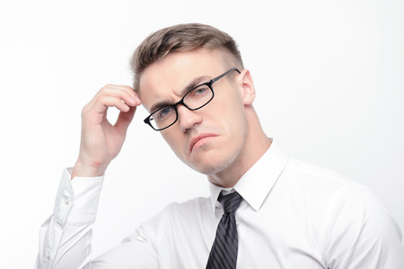 youthful: Thinking about problems. Portrait of youthful attractive serious businessman standing on white isolated background with fingers near his head.