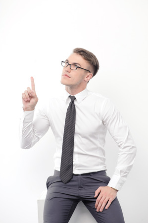 youthful: Here it is. Portrait of youthful attractive businessman standing on white isolated background and pointing with his index finger upwards. Stock Photo