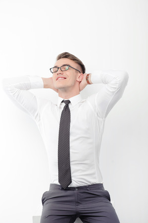 arms behind head: Time to relax. Portrait of young-looking handsome businessman wearing glasses on white isolated background with arms behind his head.