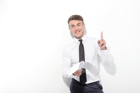 youthful: Brilliant idea. Youthful attractive businessman standing on white isolated background holding papers and pointing up with index finger. Stock Photo