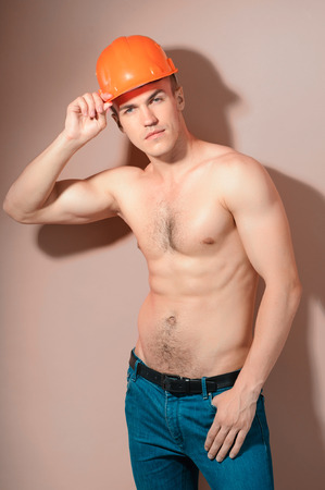 seins nus: Constructeur Séduisant. Portrait de beau jeune homme torse nu portant un chapeau dur et posant sur le fond isolé Banque d'images