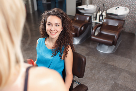 upbeat: I need to look perfect. Upbeat pleasant dark haired client sitting in the chair while discussing haircut with professional  hairdresser. Stock Photo