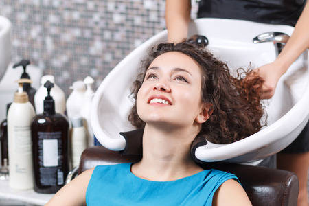 good feeling: Good feeling. Close up of attractive young lady leaning her head backwards and smiling while having  hair washed in beauty salon