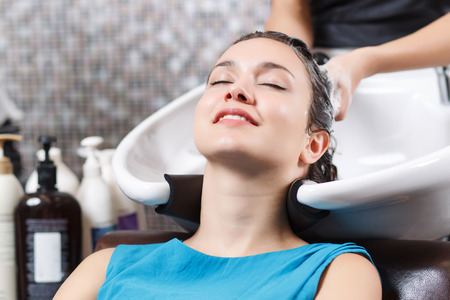 eyes closing: Pleasant feeling. Close up of attractive pleasant young woman leaning the head on washbasin and closing  eyes of pleasure while professional hairdresser washing  her head Foto de archivo
