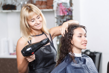 hairdresser: Doing with love. Vivacious nice professional hairdresser holding hairdryer and  touching hair of client while going to do hairstyle.