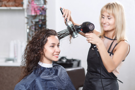 hairstyle: Best hairstyle. Pleasant attractive hairdresser holding hairdryer and comb and looking at client while drying hair.