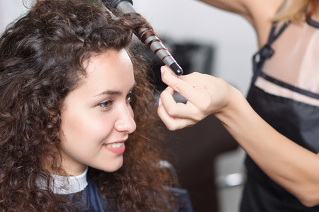 upbeat: Lets make beautiful curls. Professional pleasant hairdresser holding curling and rolling hair of smiling upbeat client. Stock Photo