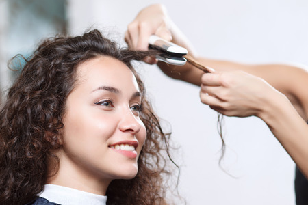 vivacious: Doing well. Selective focus of professional hairdresser holding hair iron and  making hairstyle to pleasant vivacious client sitting in the chair. Stock Photo