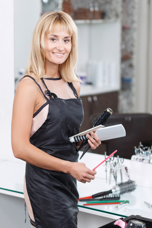 upbeat: Love my job. Pleasant upbeat professional hairdresser smiling and keeping hairdressing devices while expressing positivity.