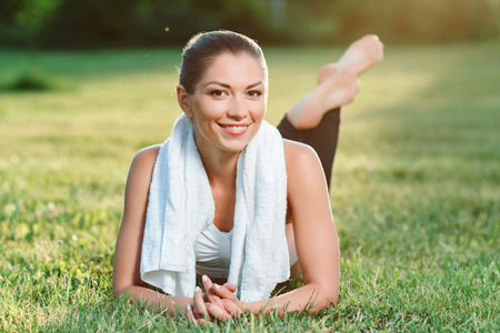 upbeat: Feeling glad. Upbeat young woman holding her hands together and lying on the grass while relaxing.