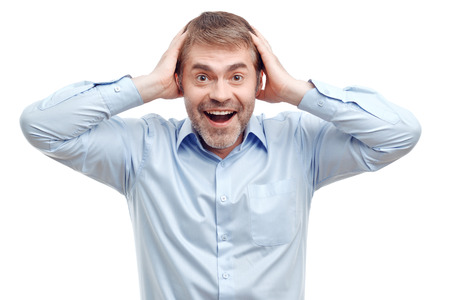 upbeat: Overwhelming positivity.  Cheerful upbeat adult man touching his head with both hands and smiling while feeling illuminated.