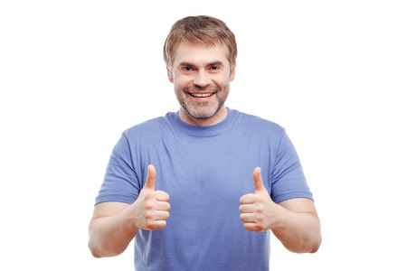upbeat: Life is good. Pleasant upbeat smiling adult man holding hand in front of him and thumbing up while evincing positivity