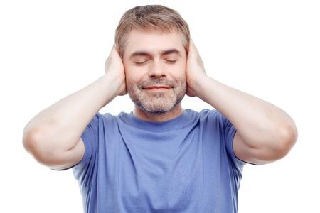 oido: Disfruta del silencio. Hombre relajado agradable la celebración de su mano en los oídos y cerrar los ojos mientras regocijo en la relajación.