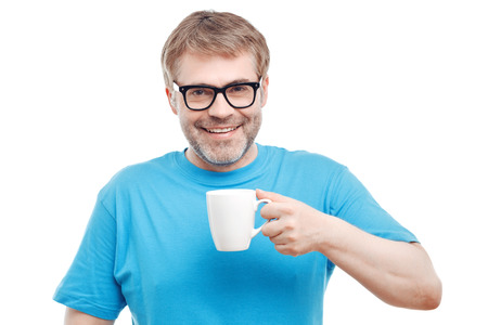 agreeable: Unforgettable aroma. Agreeable positive adult man holding cup of tea and smelling flavor while drinking it.