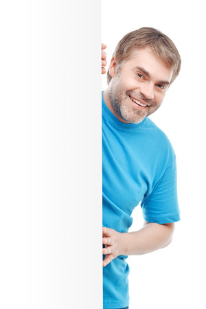 i am here: I am here. Pleasant vivacious adult man touching the wall and looking out of it while standing isolated on white background. Stock Photo