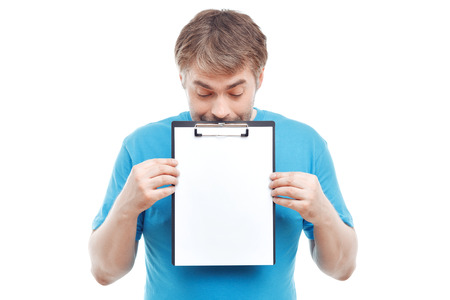 glance: Have a look.  Nice positive man holding folder and keeping his glance down while standing isolated on white background