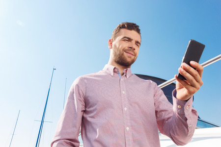 businessman waiting call: Waiting for good news. Positive smiling businessman holding mobile phone and going to make call while standing near his yacht