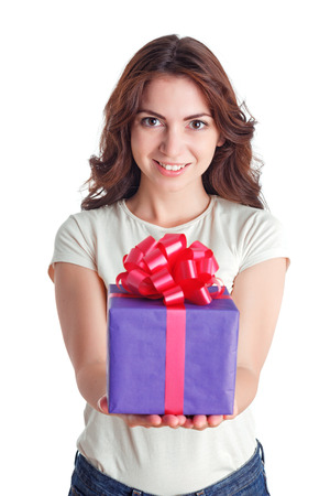 upbeat: Here you are. Waist up of pretty upbeat girl keeping hands in front of her and holding present in them while smiling.