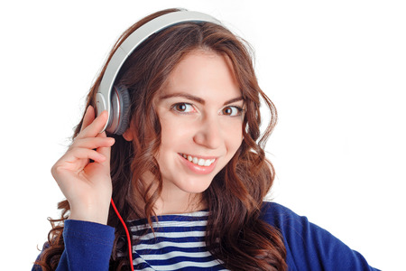 laugher: Music in my mind. Portrait of positive smiling beautiful girl wearing headphones and touching it while listening to music. Stock Photo