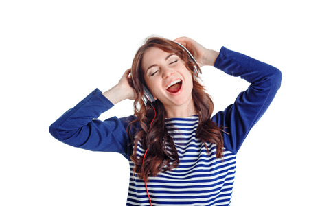laugher: Be yourself. Exited young beautiful girl holding hands on the headphones and closing her eyes  while reveling in listening to music