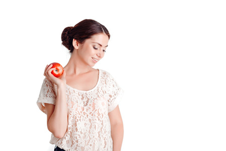 upbeat: Healthy lifestyle.  Upbeat smiling beautiful girl holding apple in one hand and keeping her glance down while expressing positivity. Stock Photo