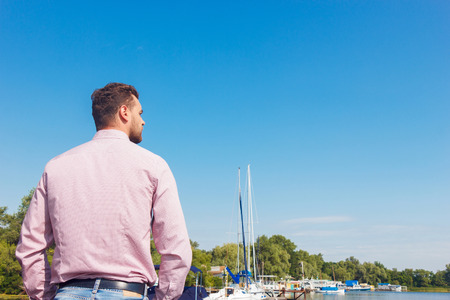 laugher: Where to sail. Pleasant man holding his hands in pockets and mulling over while standing turned backwards. Stock Photo