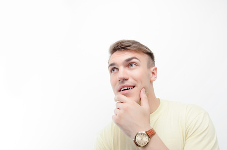 youthful: Being thoughtful. Close up portrait of youthful handsome man  on white isolated background touching his chin with his fingers Stock Photo