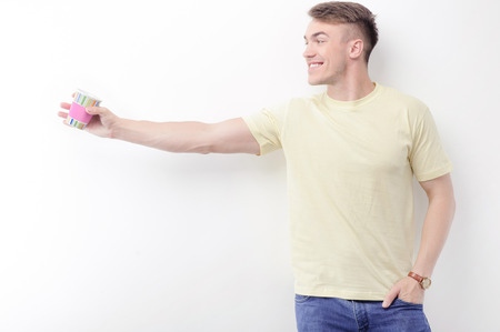 guy standing: Look there. Portrait of young smiling guy standing on white isolated background and pointing aside with colorful paper cup