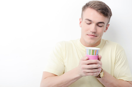 youthful: Holding careful. Portrait of youthful attractive guy on white isolated background holding paper cup.