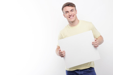 youthful: Place for advertisement. Handsome youthful smiling man standing with sheet of white paper on isolated background