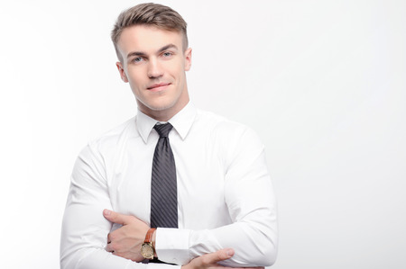 sensational: So serious. Portrait of young-looking businessman standing with crossed arms on white isolated background.