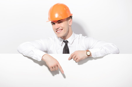 Look down. Man wearing hard hat standing behind white board and pointing with his index finger down