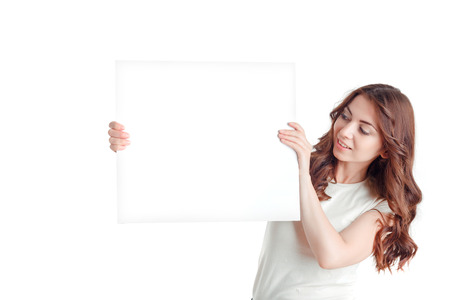 upbeat: Look on it. Nice upbeat beautiful young girl holding white board and looking at it while evincing positive emotions. Stock Photo