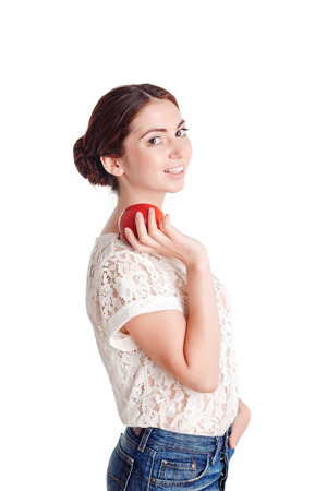 laugher: Good choice.  Pleasant  beautiful young girl holding hand in pocket and keeping apple  while standing positive half turned. Stock Photo