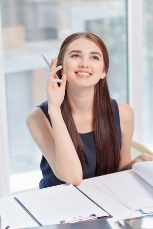 laugher: Time to think. Smiling beautiful business woman holding pen and sitting at the table while thinking