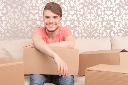 upbeat: Ready to pack. Upbeat merry young husband sitting on the sofa and holding box while feeling euphoric.