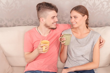 vivacious: Enjoy the aroma. Content vivacious young couple drinking tea and sitting on the sofa while bonding to each other. Stock Photo
